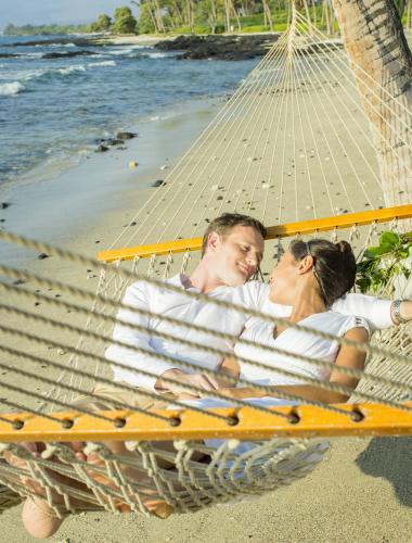 Romantic honeymoon couple in a hammock on the beach on Lanai